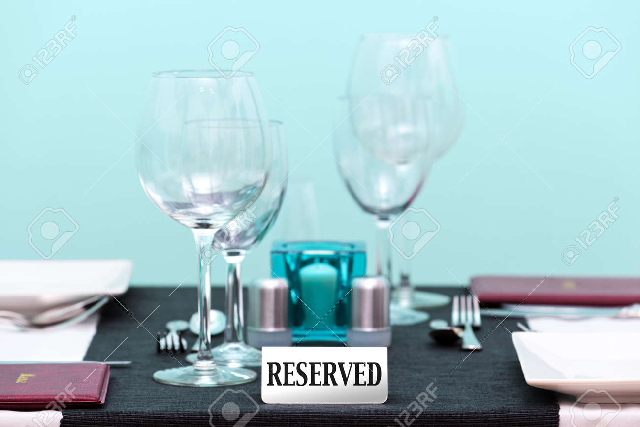 Photo of the reserved sign on a restaurant table setting. Focus is on the sign with a very shallow depth of field. Stock Photo - 12194715