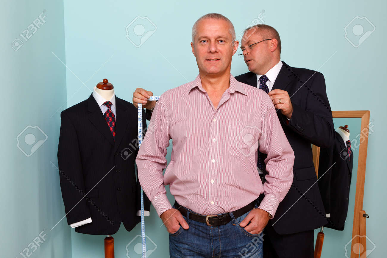 Photo of a tailor measuring the shoulder width of a man for the fitting of a new bespoke suit - 12382302