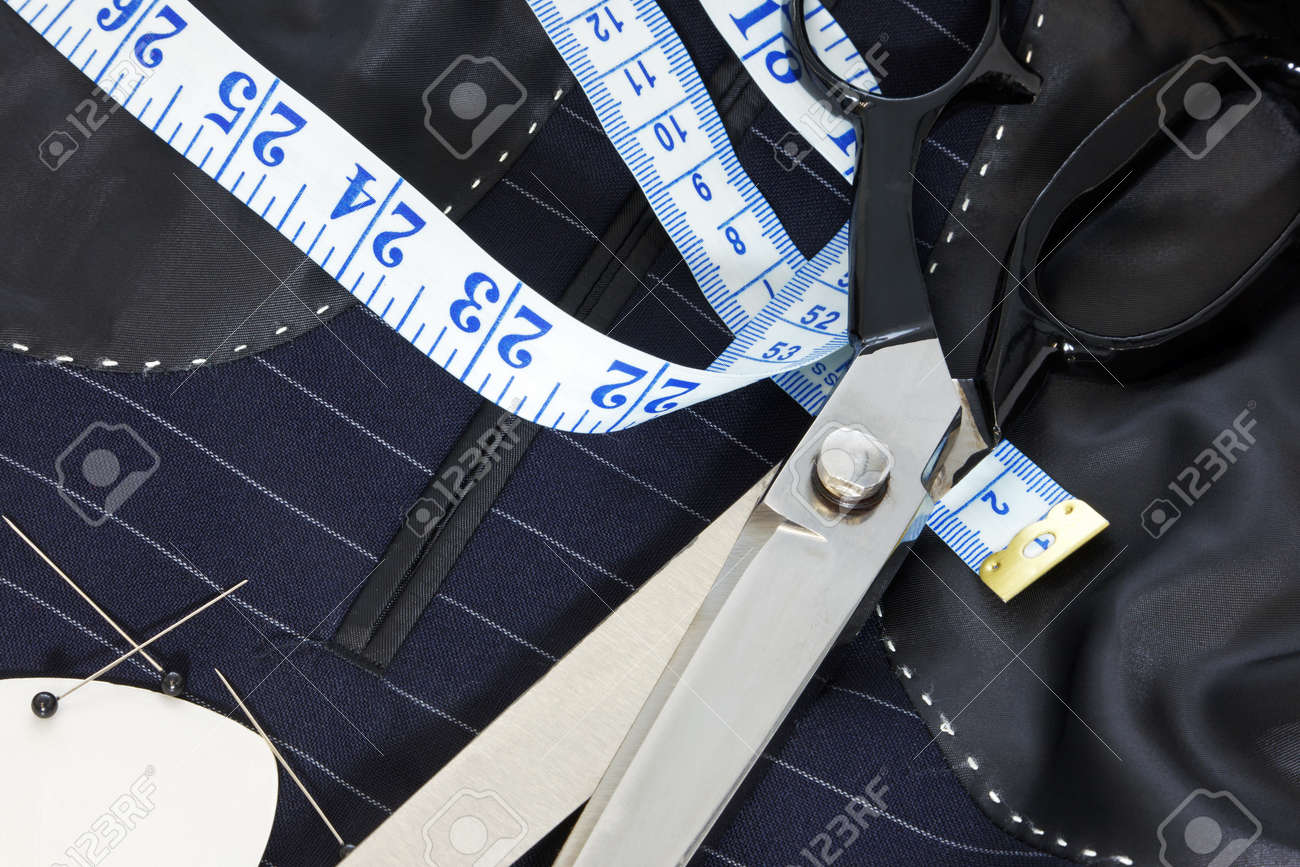 Still life photo of the inside of a bespoke suit jacket with hand stitching and scissors, tape measure, chalk and pins. - 12382312