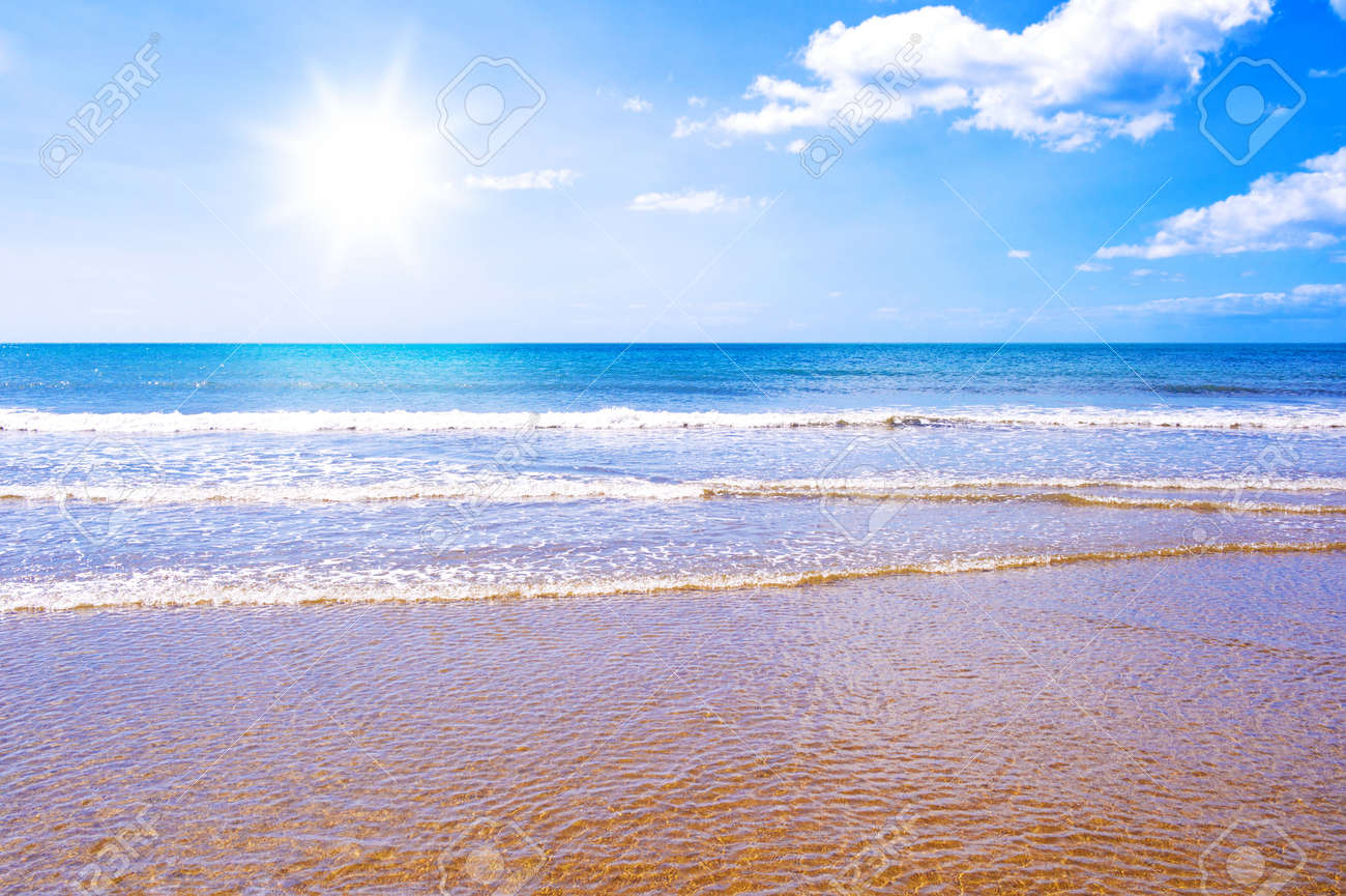 Photo of waves crashing on a golden beach with the sun shining in a blue sky Stock Photo - 13203177
