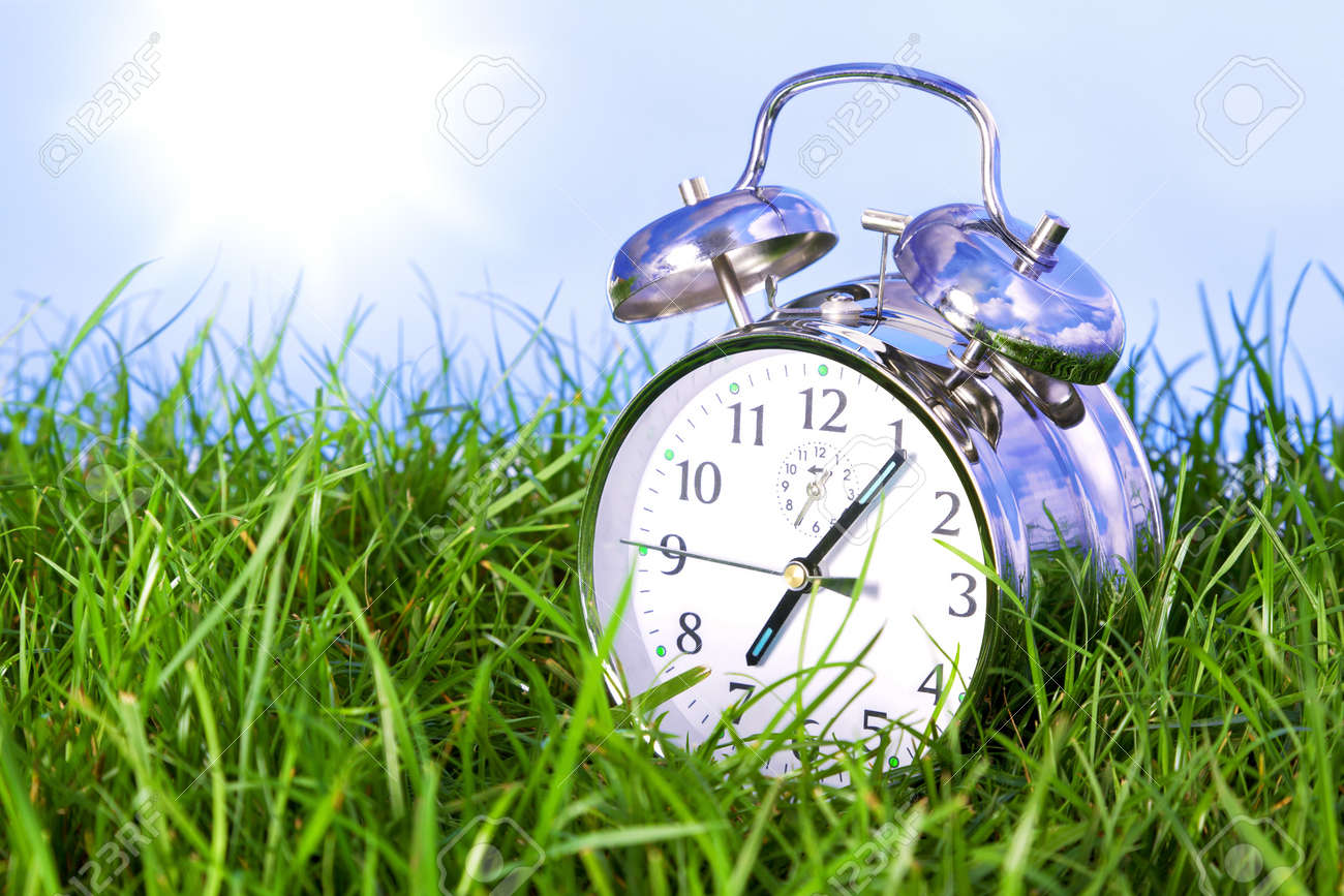 Photo of a chrome alarm clock outdoors sitting in grass on the morning of a bright sunny day. Stock Photo - 13203181