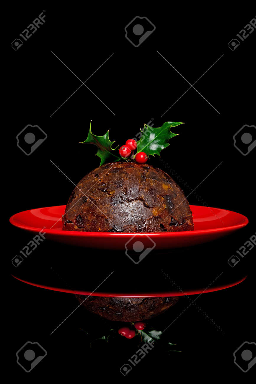 Photo of a traditional Christmas pudding with holly and berries on top, on a black background. Stock Photo - 15397210