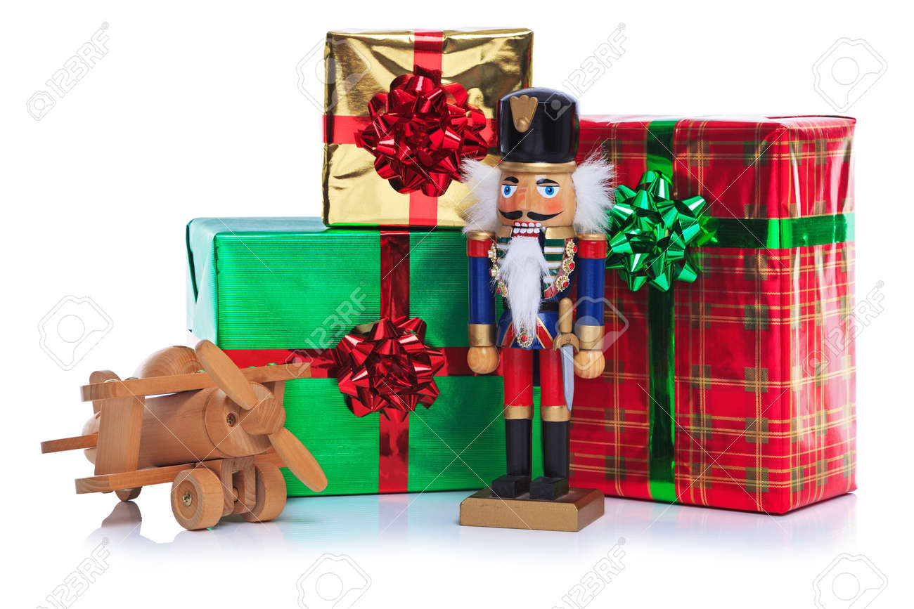 Photo of a christmas toy wooden soldier with wooden plane and photo of a christmas toy wooden soldier with wooden plane and other gift wrapped presents negle Choice Image