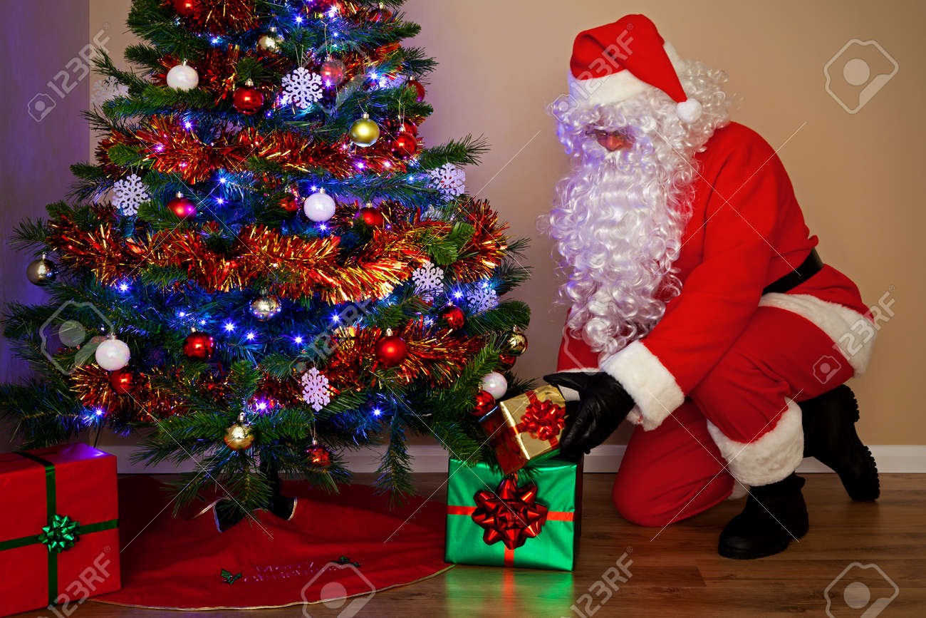 Santas Claus Delivering Presents And Putting The Gifts Under.. Stock ...