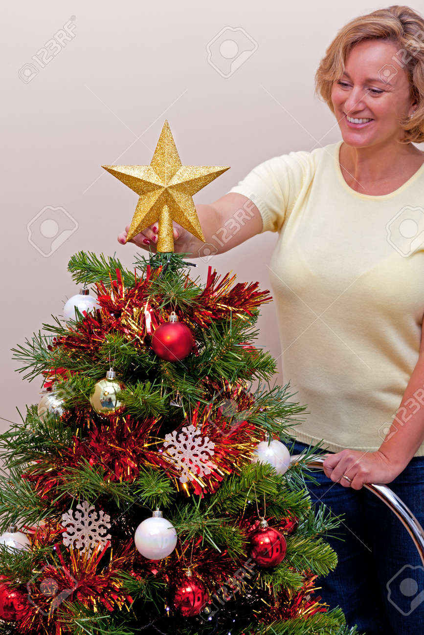 A Star For Christmas.Woman Standing On A Ladder Placing The Star On Top Of Her Christmas