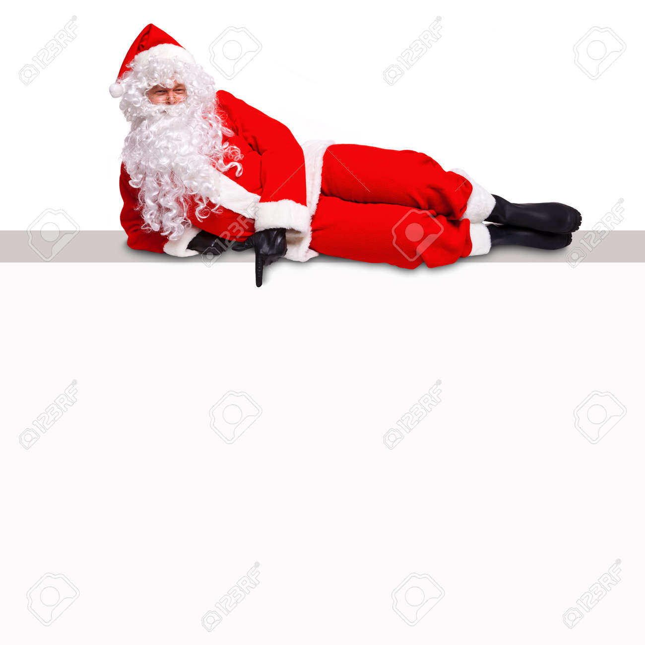 Santa Claus lying on top of a blank billboard sign pointing at an empty white area where you can add your own text. Stock Photo - 16762813
