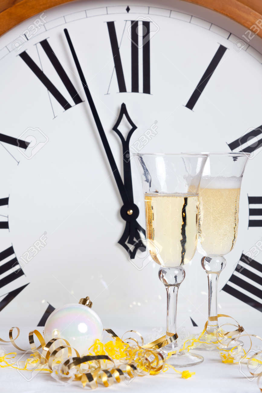 About to strike midnight on New Year Eve with champagne glasses and streamers in front of a large clock face. Stock Photo - 16761665