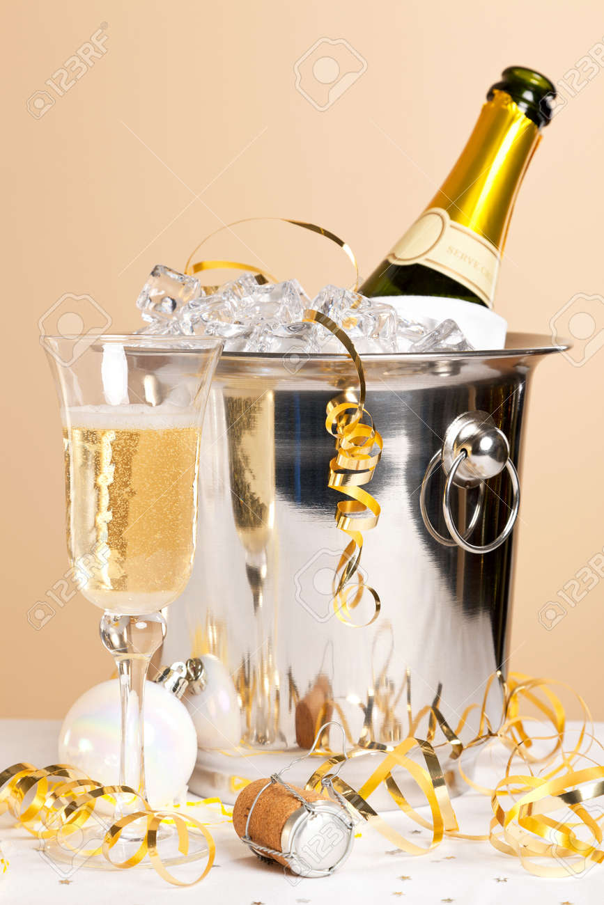 A glass of Champagne with a bottle in an ice bucket and gold streamers across the table Stock Photo - 16930921