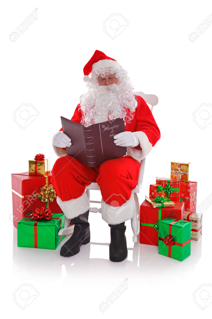 Santa Claus sat in a rocking chair surrounded by gift wrapped presents as he reads the Naught or Nice list, isolated on a white background. Stock Photo - 16828012
