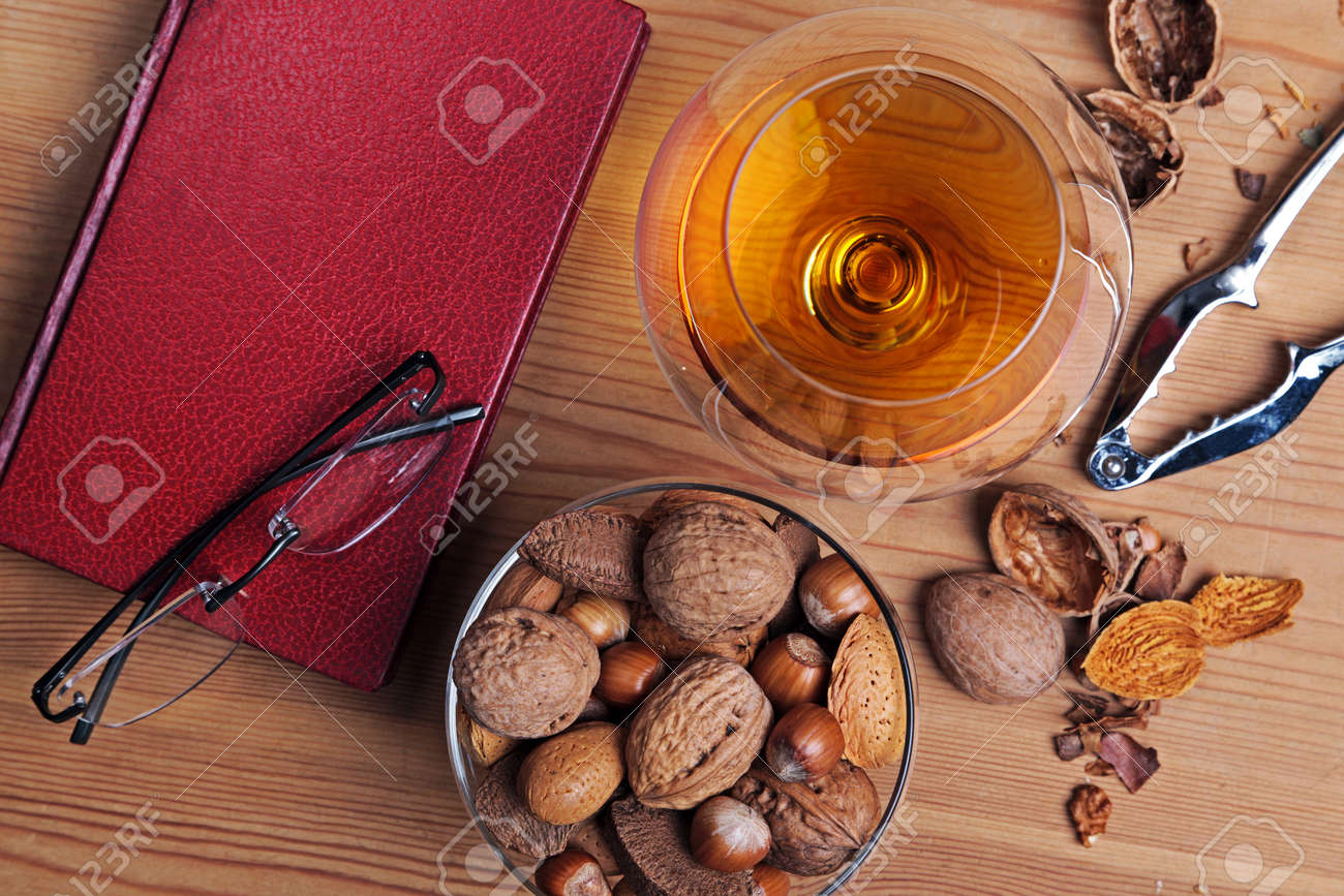 Still life photo of cognac in a crystal brandy glass with book, reading glasses and a selection of nuts on a table. Stock Photo - 16957136