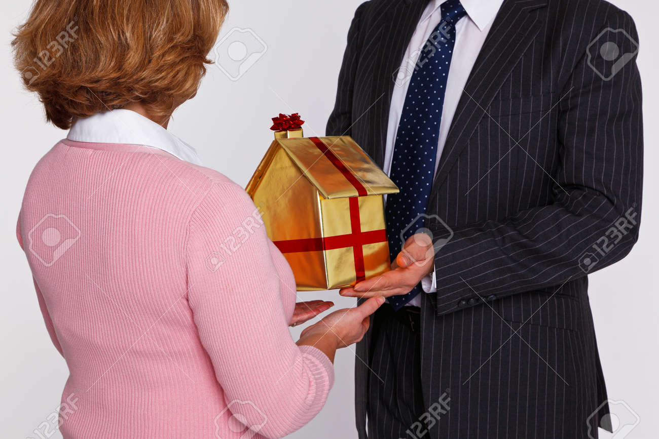 A businessman handing  a new home wrapped in gold paper with red ribbon and bow to a woman in casual clothing. Good concept image for housing and property themes. Stock Photo - 16970740