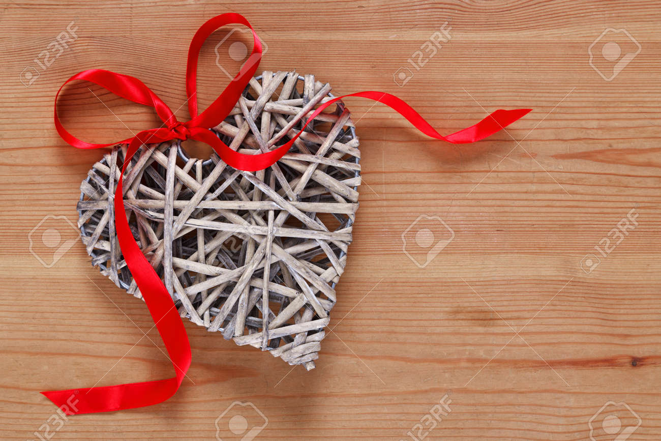 A heart shaped wicker decoration with red ribbon on a rustic wooden background. Stock Photo - 16957146