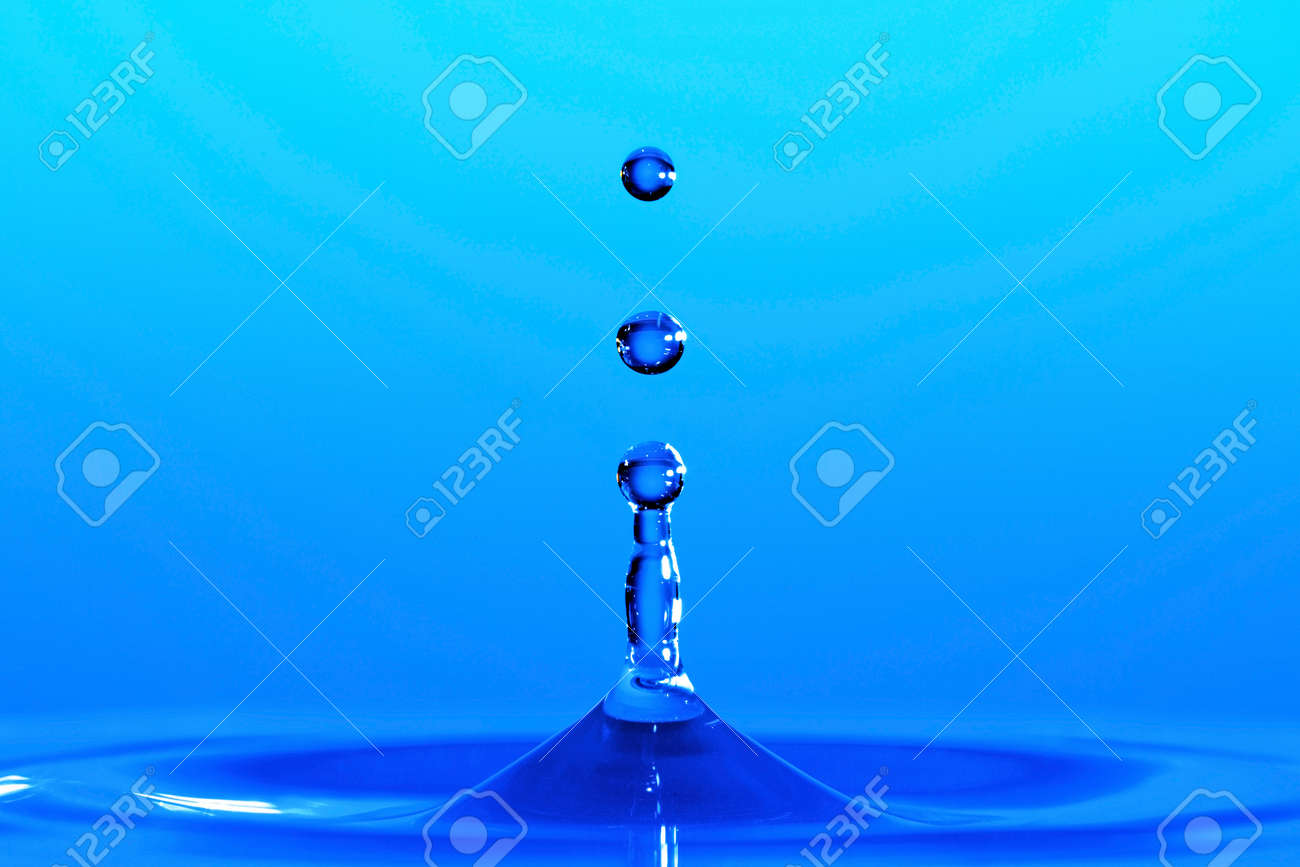 Water droplets frozen at high speed as they emerge from the liquids surface. Stock Photo - 16957132