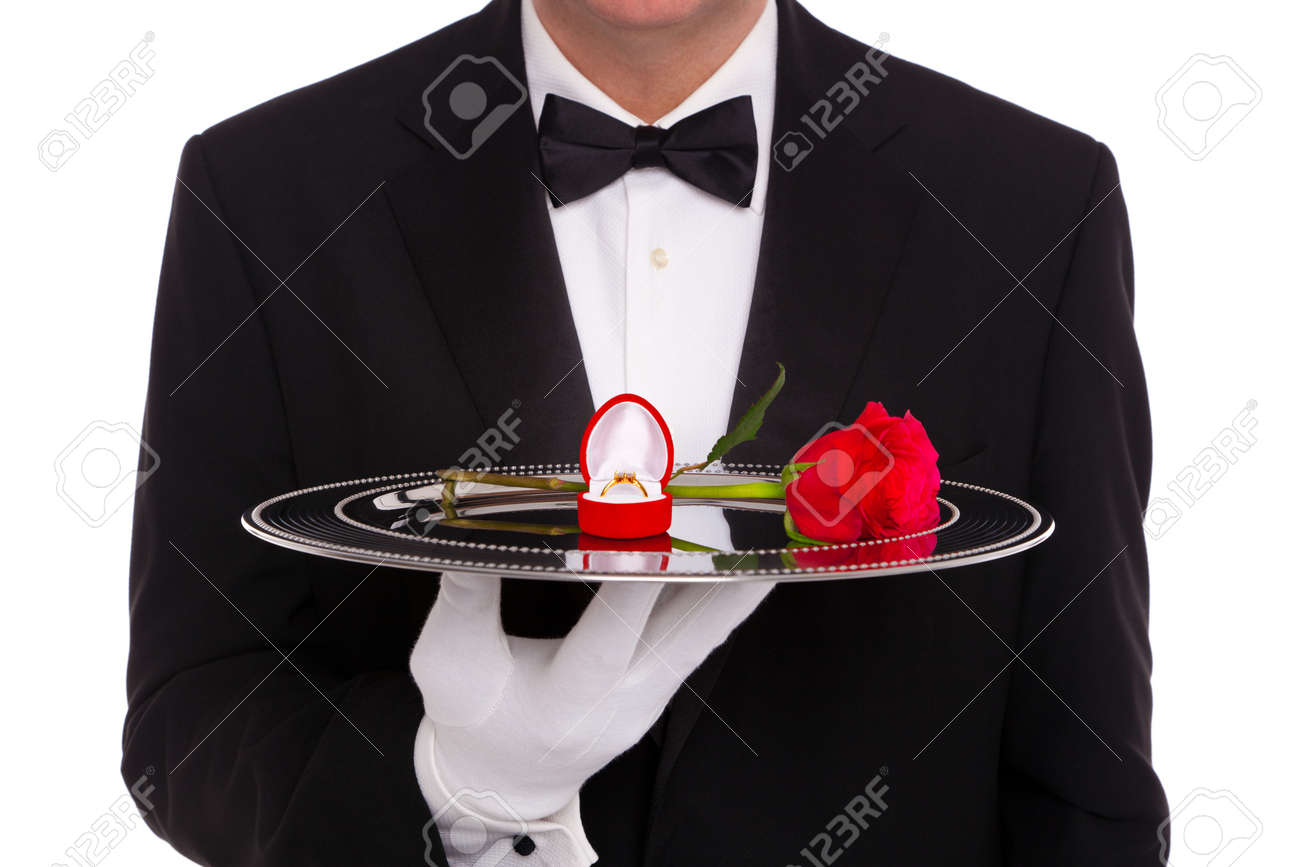 A butler holding a silver tray upon which is a diamond engagement ring in a heart shaped jewelry box and a single red rose, on a white background. - 16987375