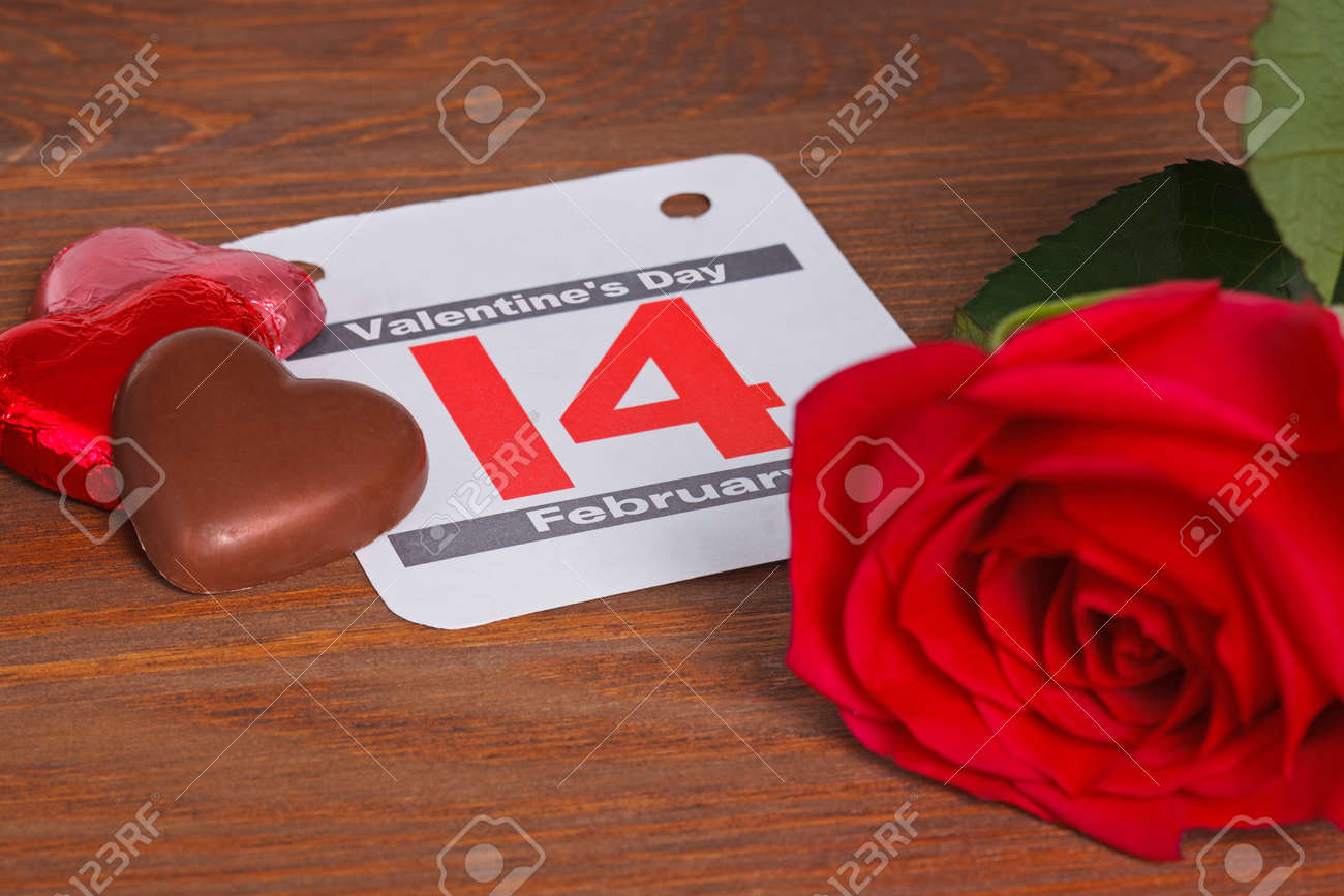 Valentines day still life photo with a calendar date for the 14th February with a single red rose and heart shaped chocolates on a wooden table. Stock Photo - 17226326