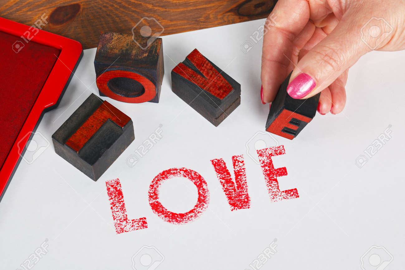 A woman using wooden letterpress blocks to print the word LOVE in red ink on white paper. Stock Photo - 17226330