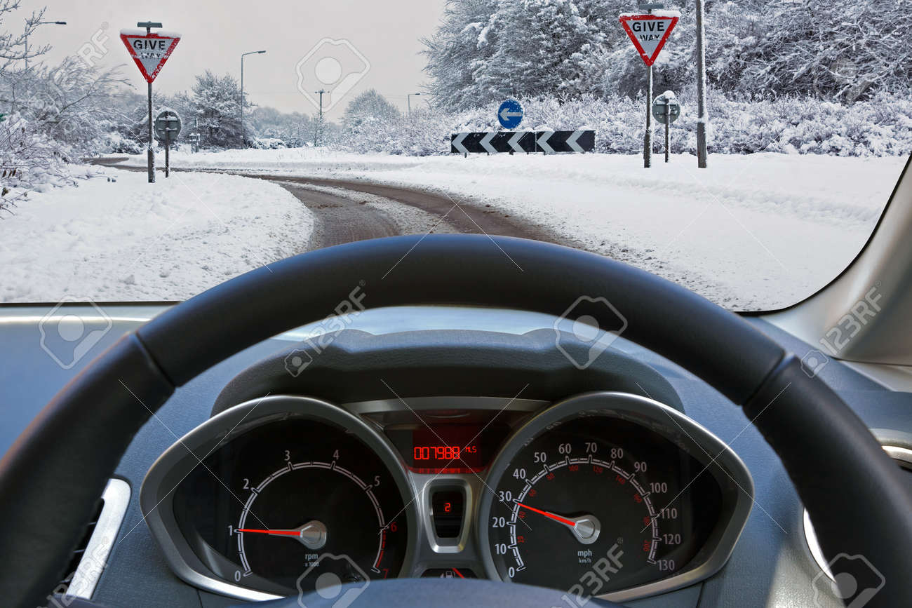 Car drivers view through the vehicle windscreen whilst driving on a snow covered road approaching a roundabout with Give Way signs, the dual carriageway has one driveable lane formed by previous motorists. Stock Photo - 17681959