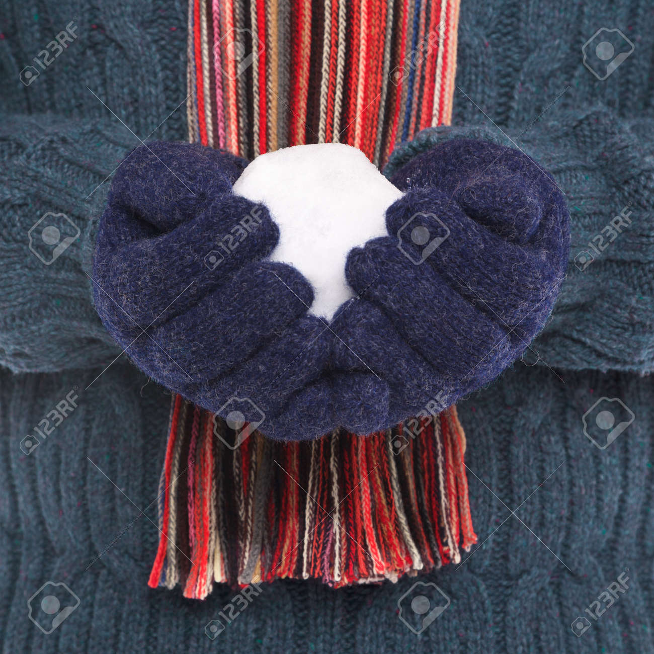 Close up of a man wearing woolen jumper, gloves and a scarf holding a snowball. Stock Photo - 17567384