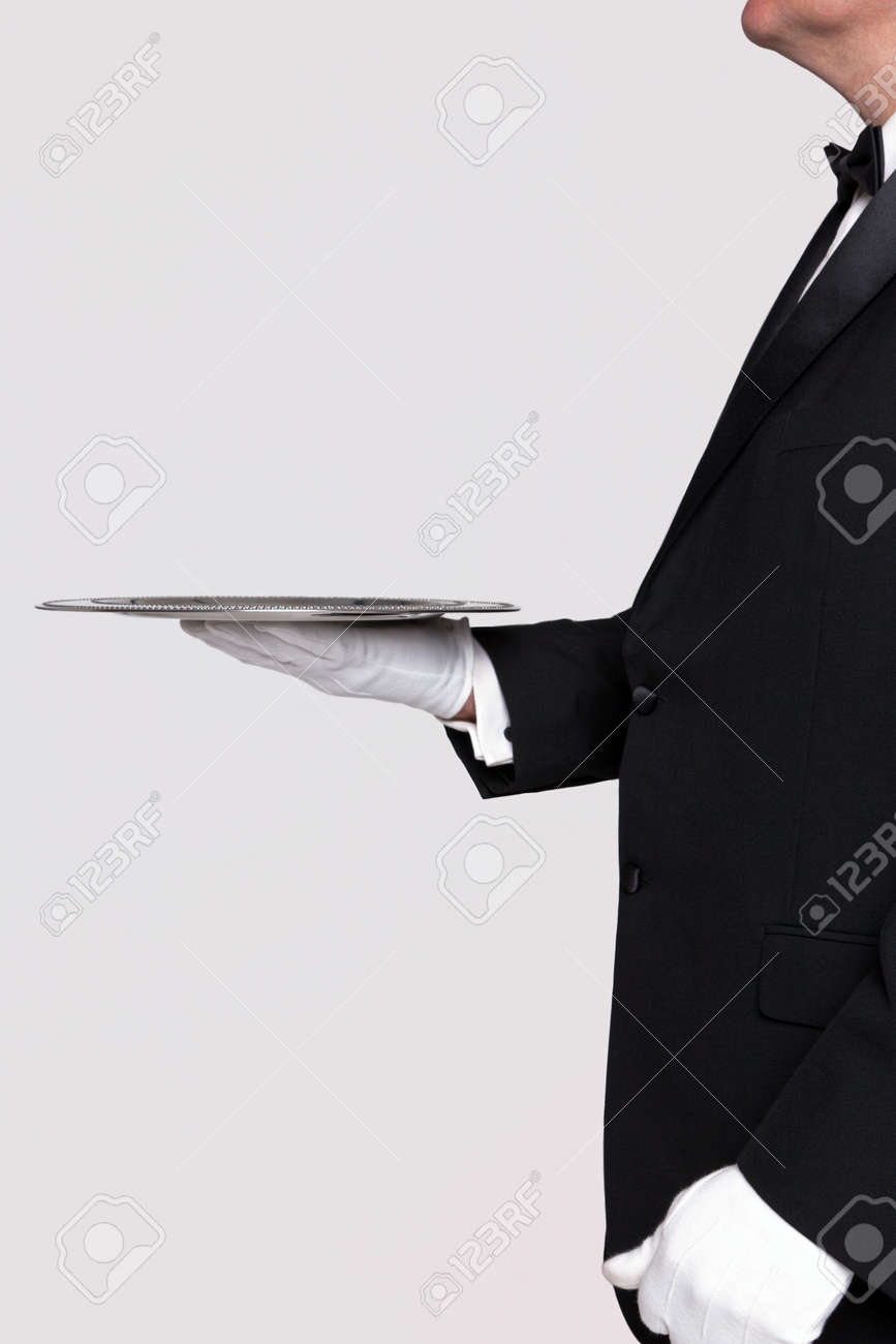 Side view of a butler holding a silver serving tray, blank background to add your own product. - 17716232