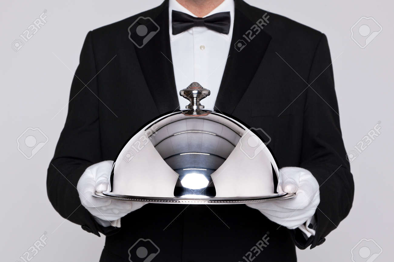 Waiter serving a meal under a silver cloche or dome - 17727197