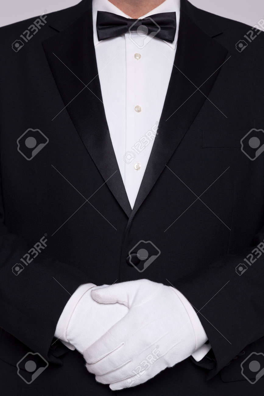 Torso of a man wearing a tuxedo with bow tie and white gloves. - 17727210