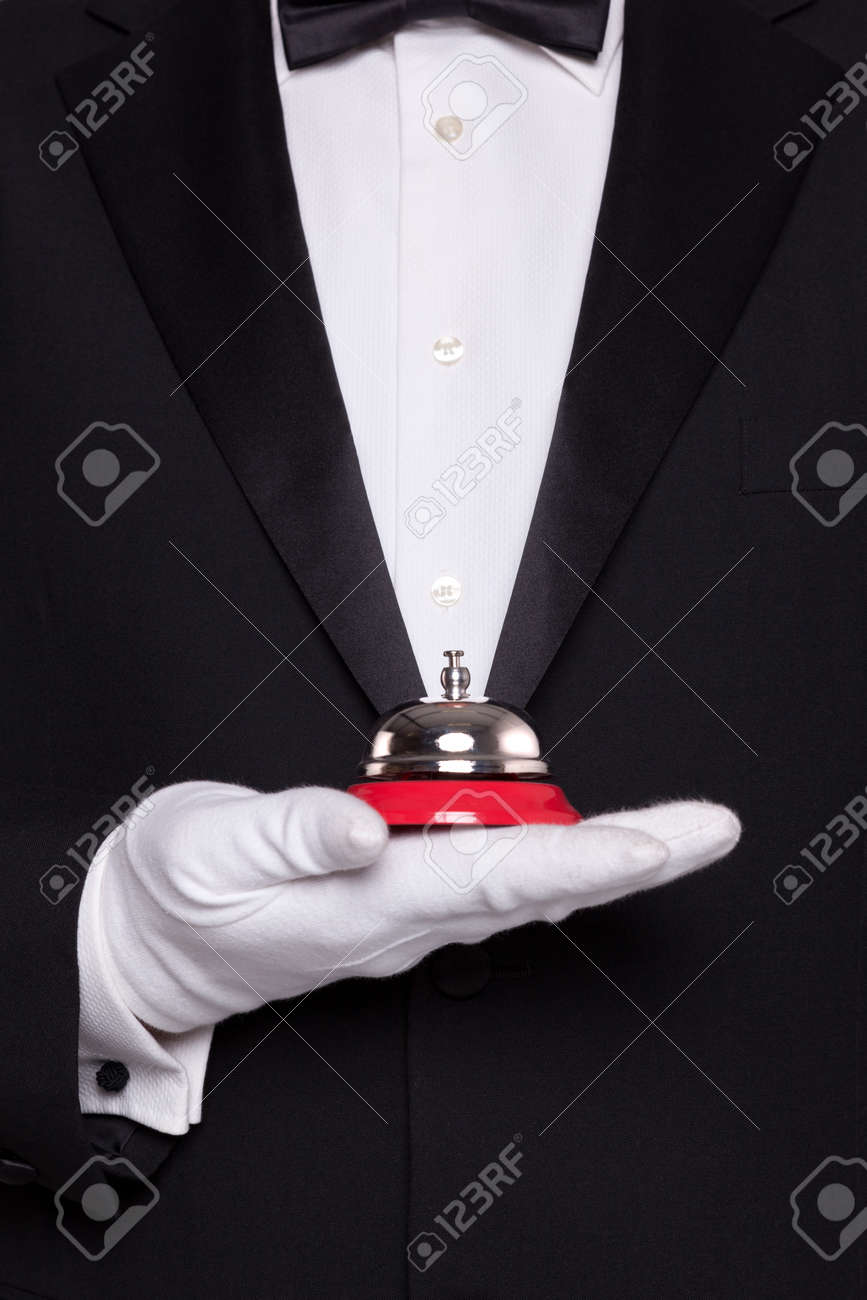 Waiter in black tie and white gloves holding a service bell. - 17715991