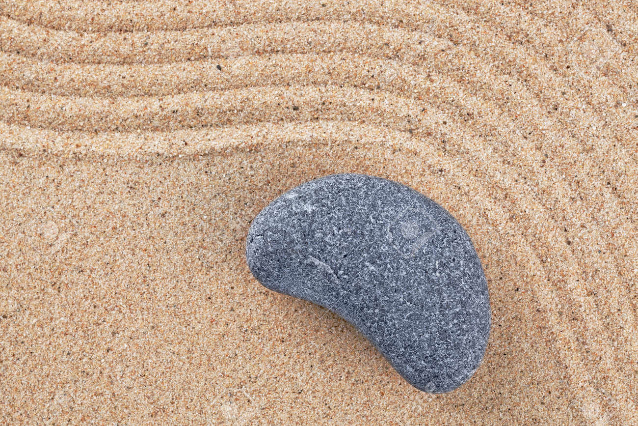 A curved pebble on a raked sand zen garden Stock Photo - 18367365