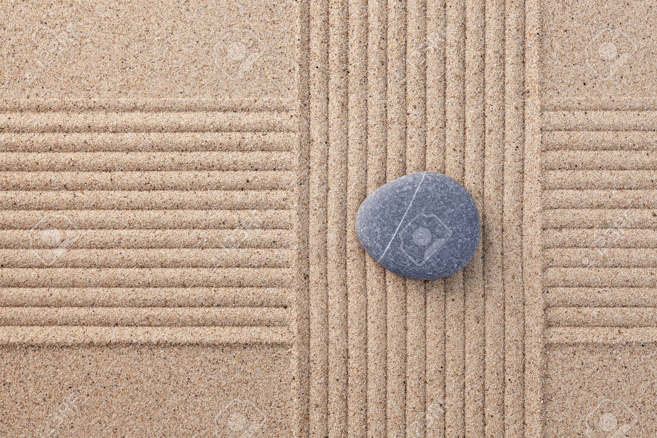 A single grey pebble on a raked sand zen garden with criss crossed sections Stock Photo - 18367368