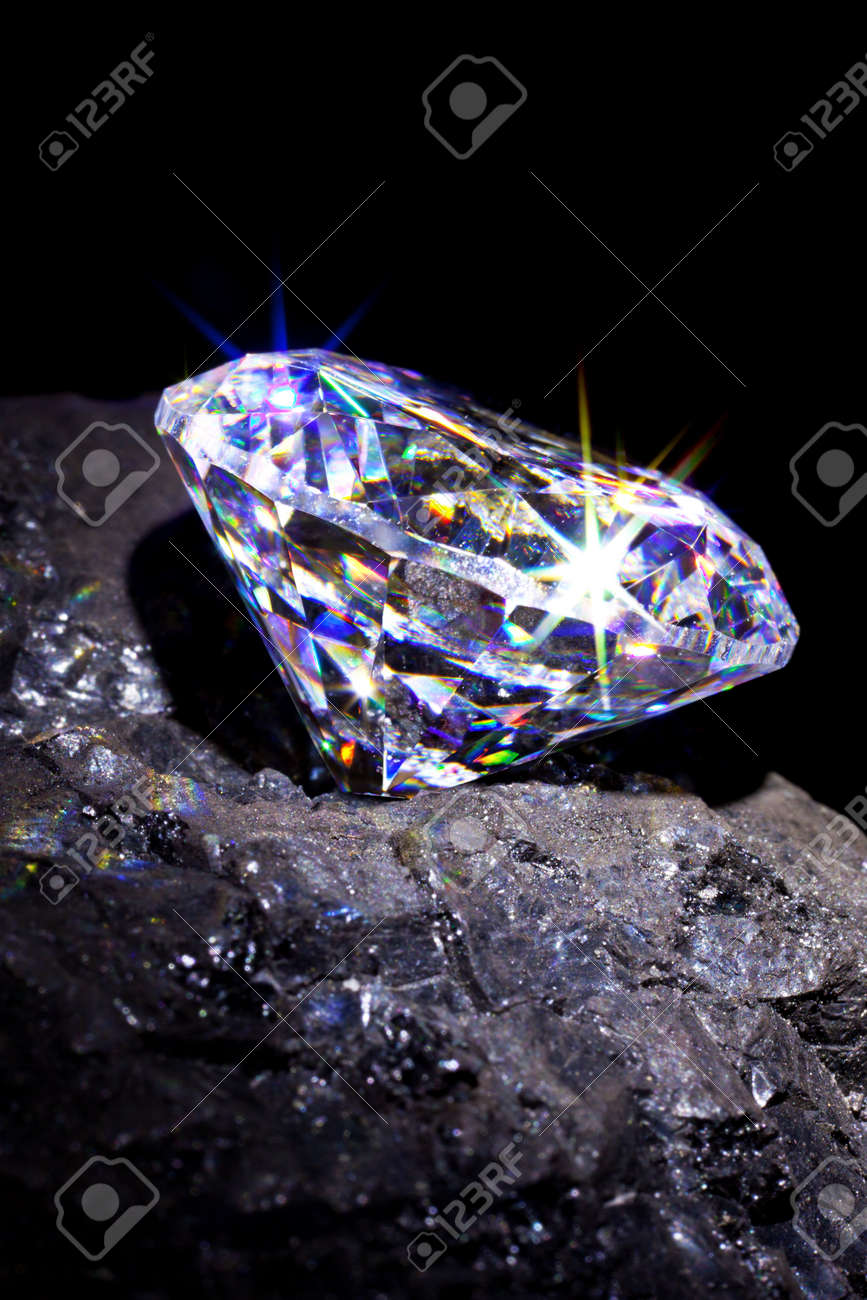 Single cut diamond on a piece of coal to symbolise them both being carbon based, studio shot taken against a black background. Stock Photo - 20162095