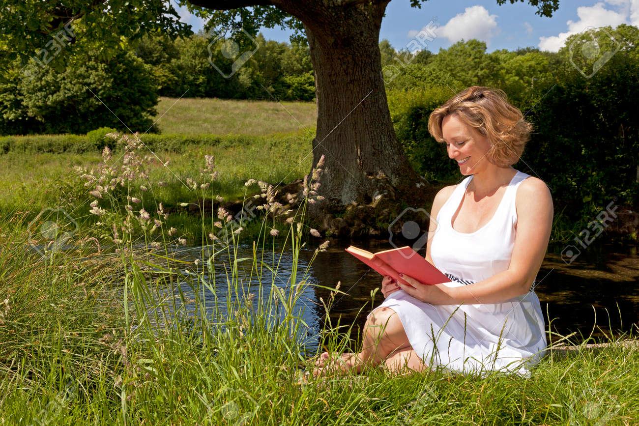D'été Lire Assis Sur Lumineux Dans Par De Livre Femme Robe Courant Une Jour Blanche Un 34AL5Rjq