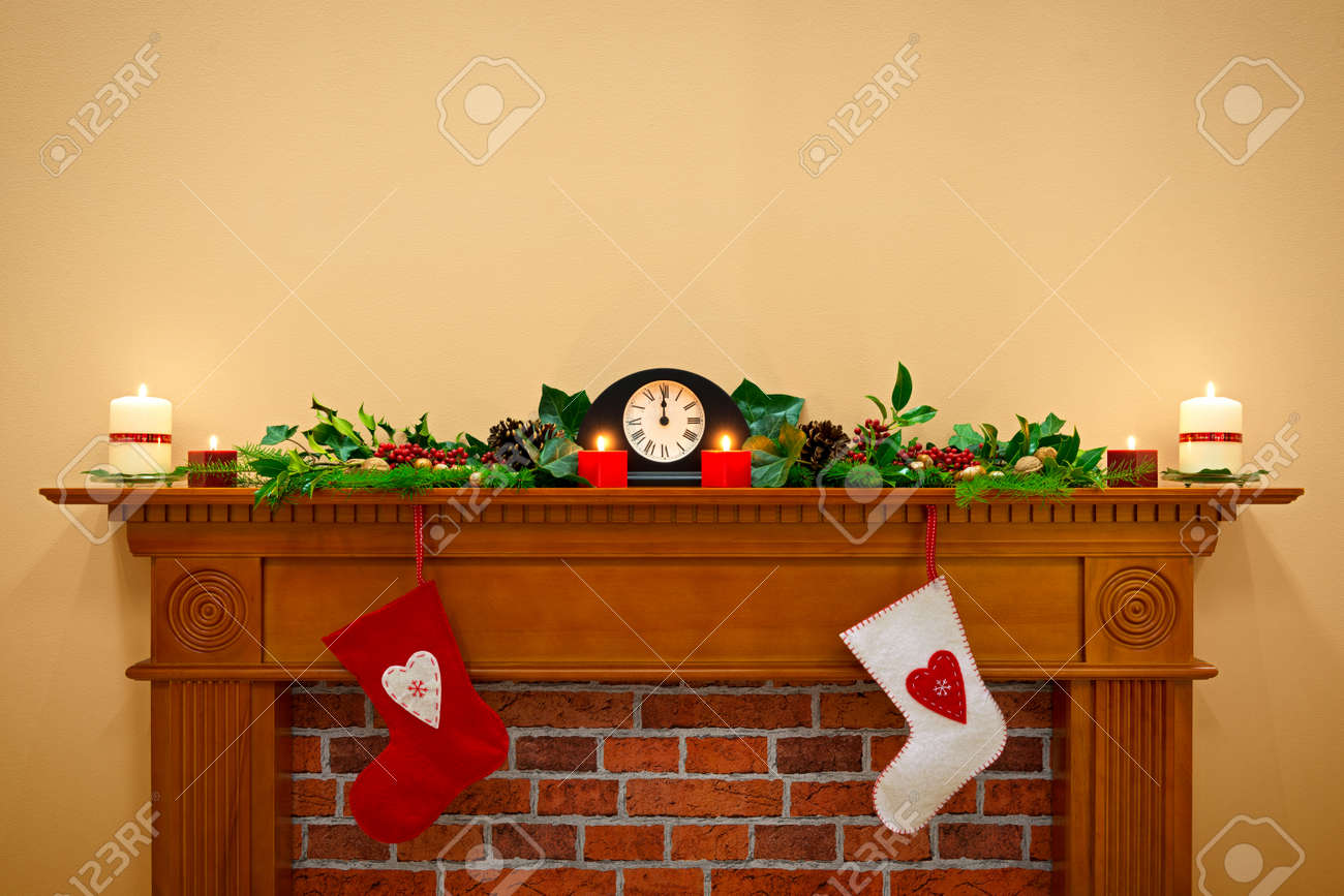 Christmas stockings hanging over the fireplace at midnight on Christmas Eve, the mantlepiece is decorated with festive holly and ivy garland plus candles. Plenty of copy space to add your own message. Stock Photo - 23721892