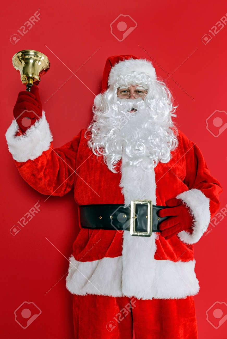 Santa Claus or Father Christmas ringing his bell against a red background. Stock Photo - 24516868