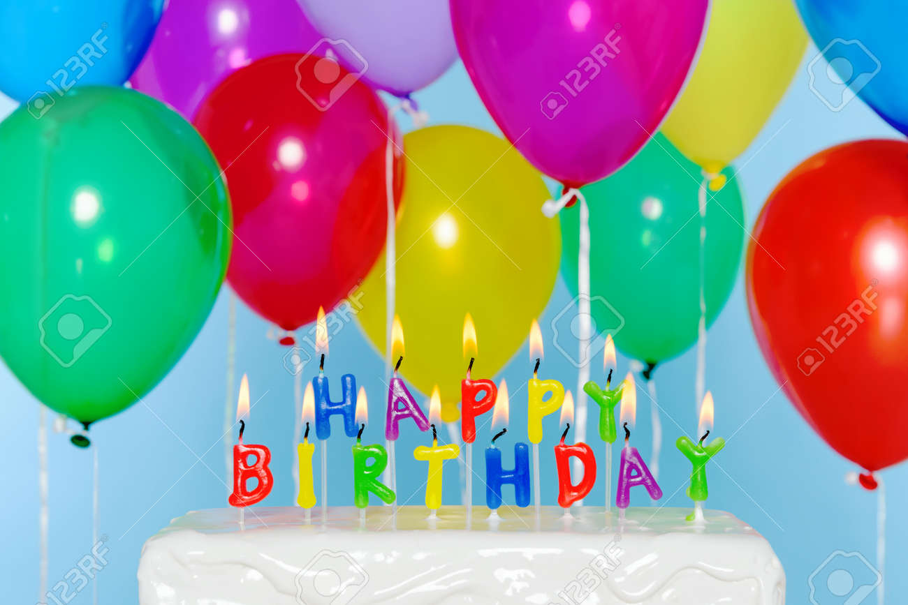 Happy Birthday Candle Letters On A Cake With Colourful Balloons In The Background Stock Photo