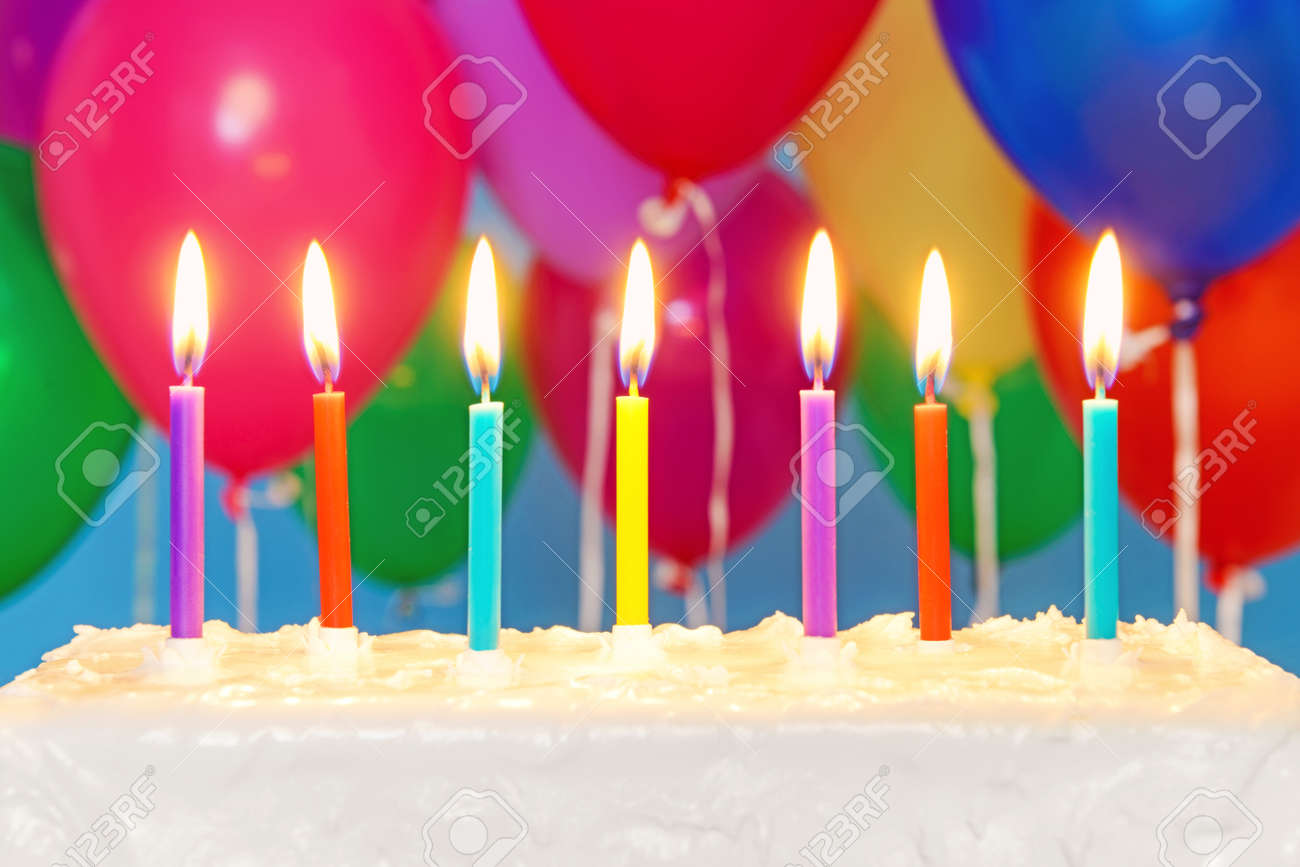 Candles Burning On An White Iced Birthday Cake With Multicoloured