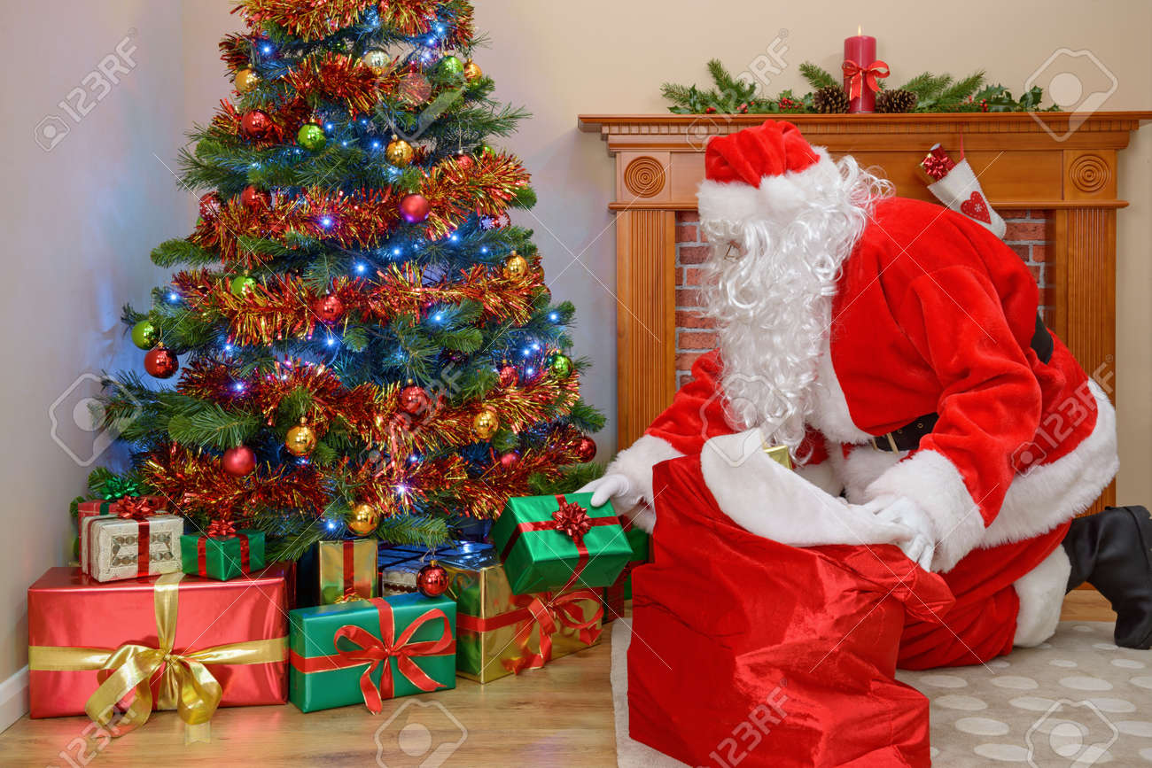 Christmas Presents Under Tree.Santa Claus Or Father Christmas Putting Presents Under Tree
