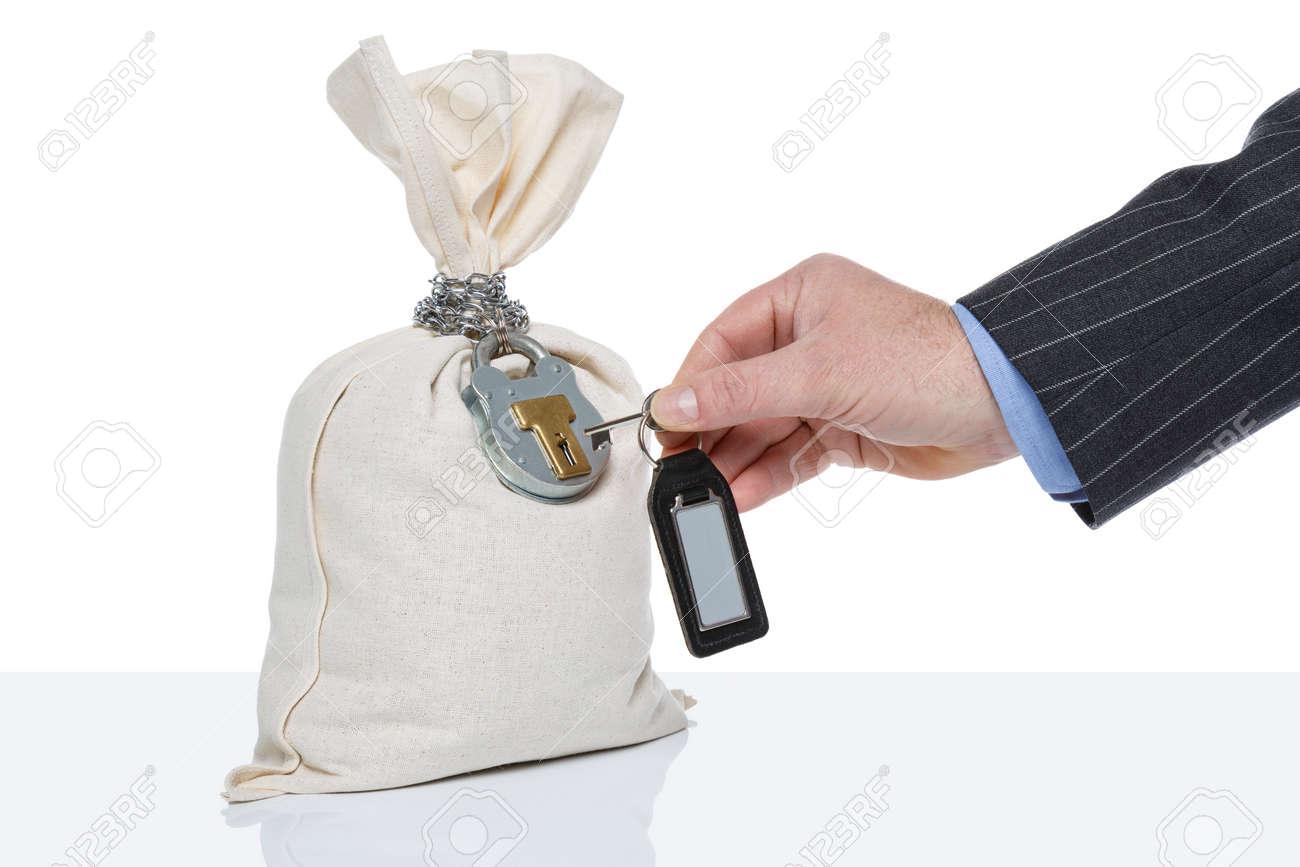 Businessman unlocking a money sack, white background, blank tag on key fob. - 43417170