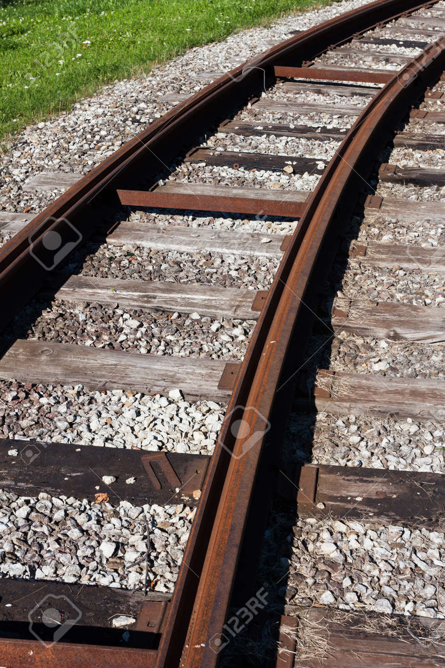 Tram rail road track disappearing around a curve in grass Stock Photo - 14784111