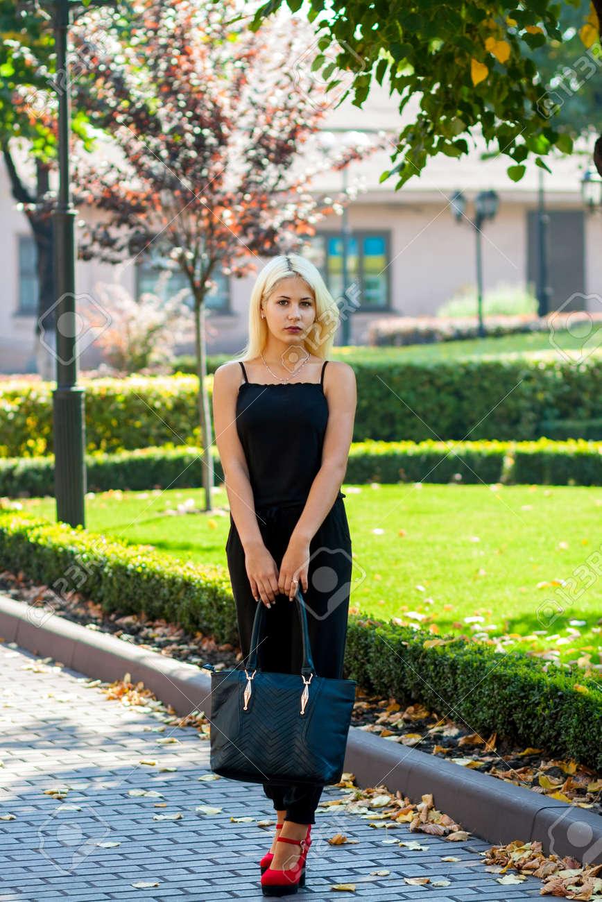 Joven Rubia Hermosa Posando En El Fondo Del Paisaje Urbano Señora Atractiva En Un Vestido Negro Y Zapatos Rojos Con Un Aspecto Agradable