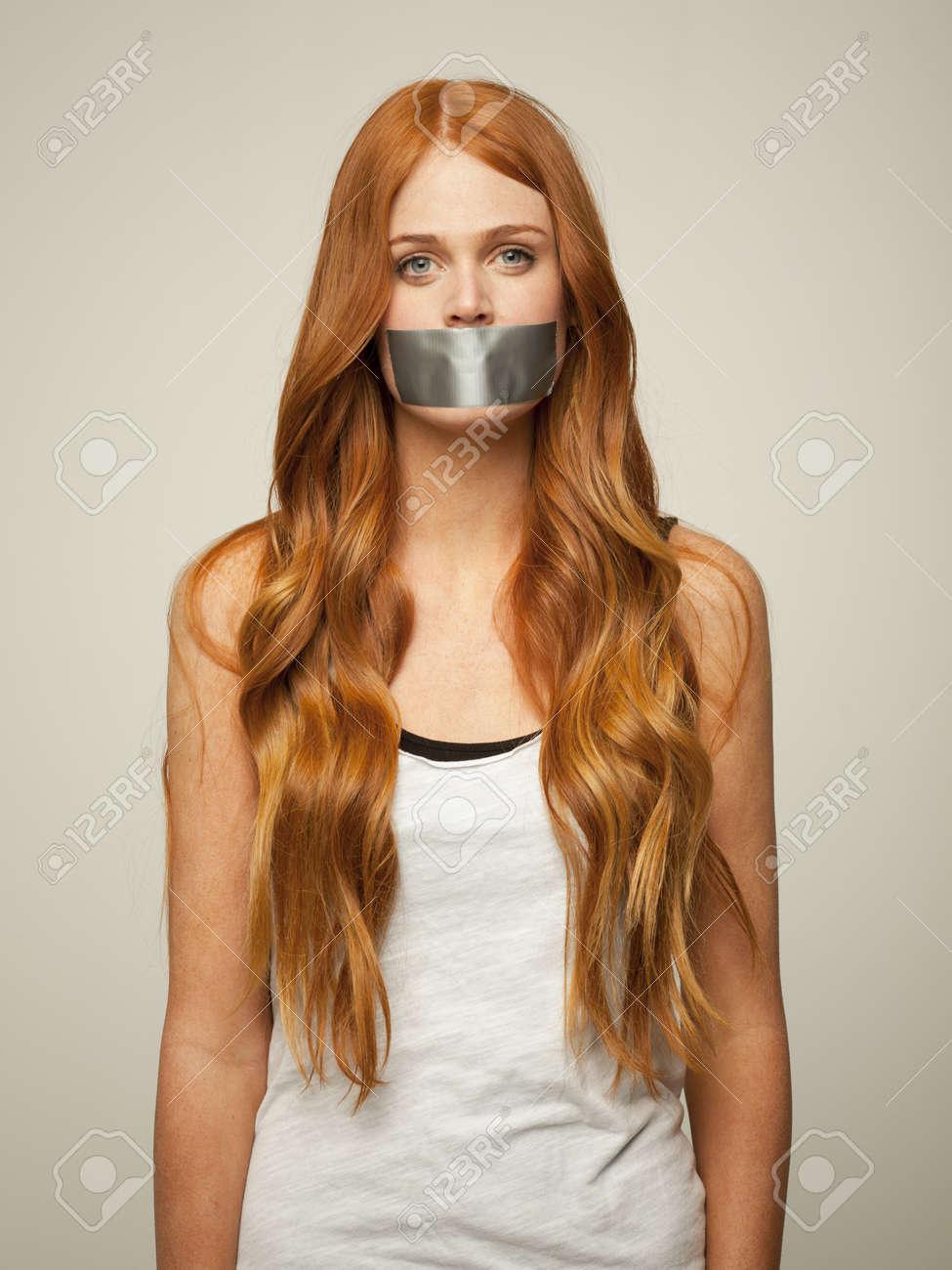 Femme Baillonnee studio photo de jeune femme bâillonnée avec du ruban adhésif