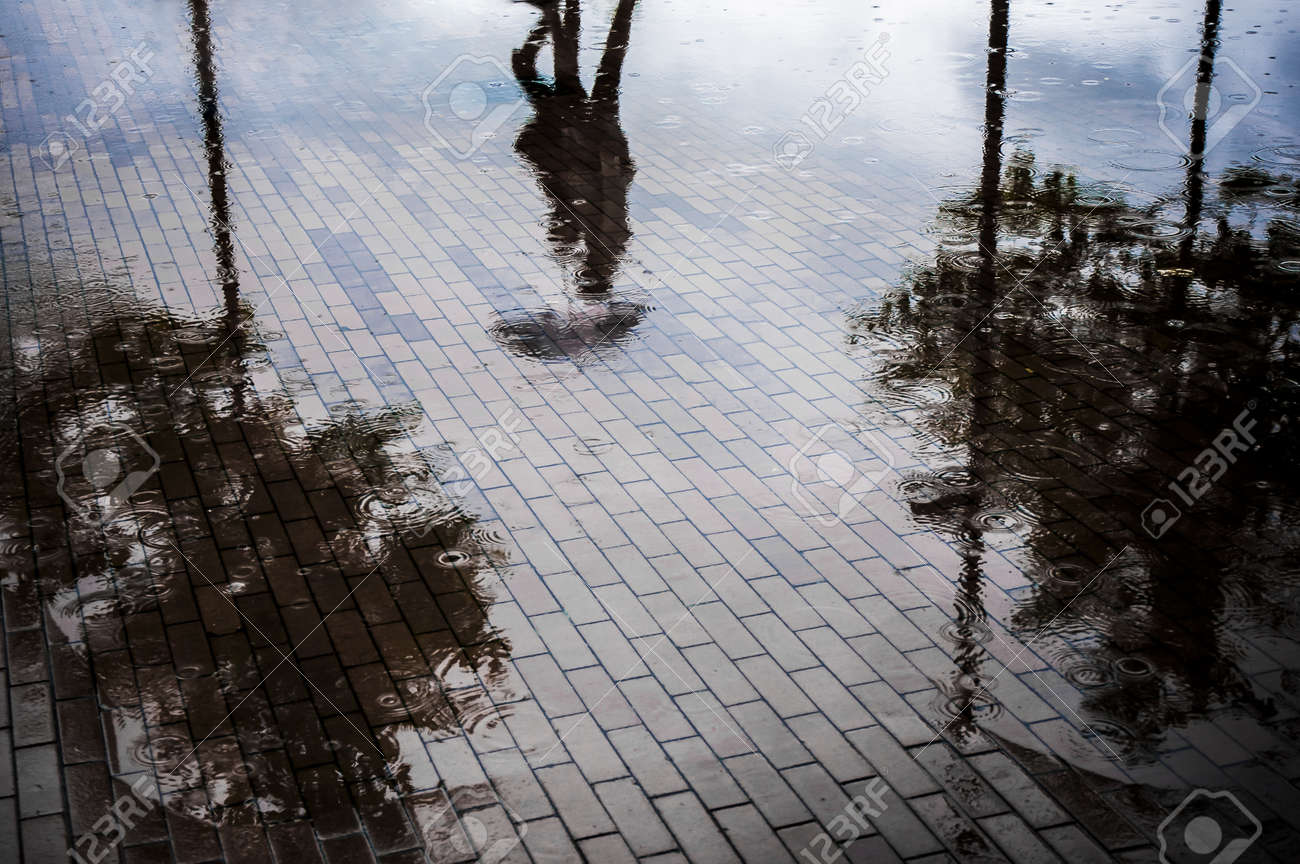 Couple with umbrella walking in reflection of flooded street after heavy rain Stock Photo - 12954312