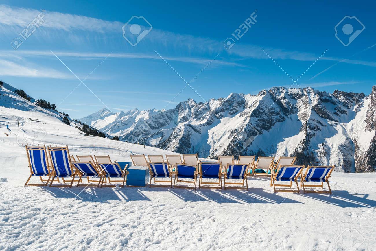 Empty Blue Deck Chairs On The Snow In Mayrhofen Ski Resort, Austrian Alps  Stock Photo