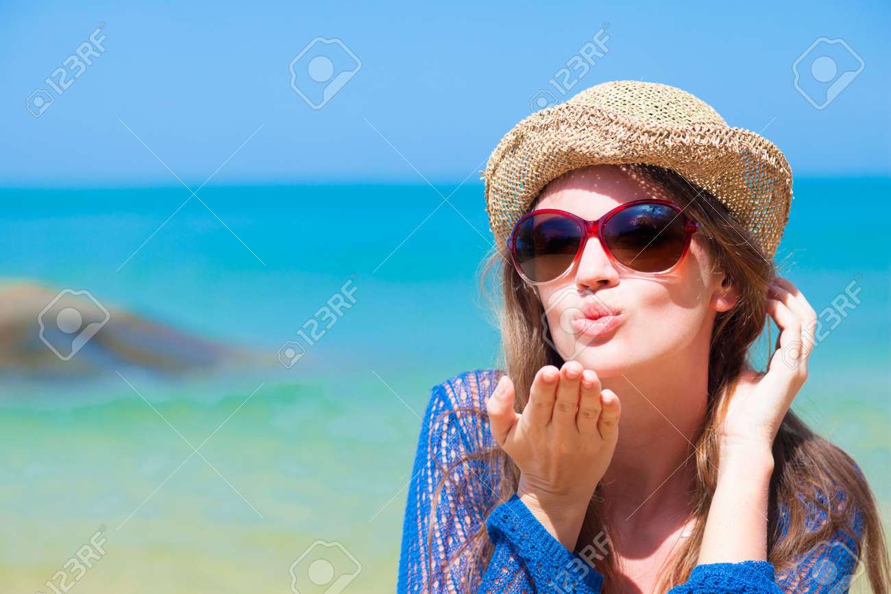7cd66a2129 portrait of young woman in sunglasses and straw hat blowing an air kiss on  beach Stock