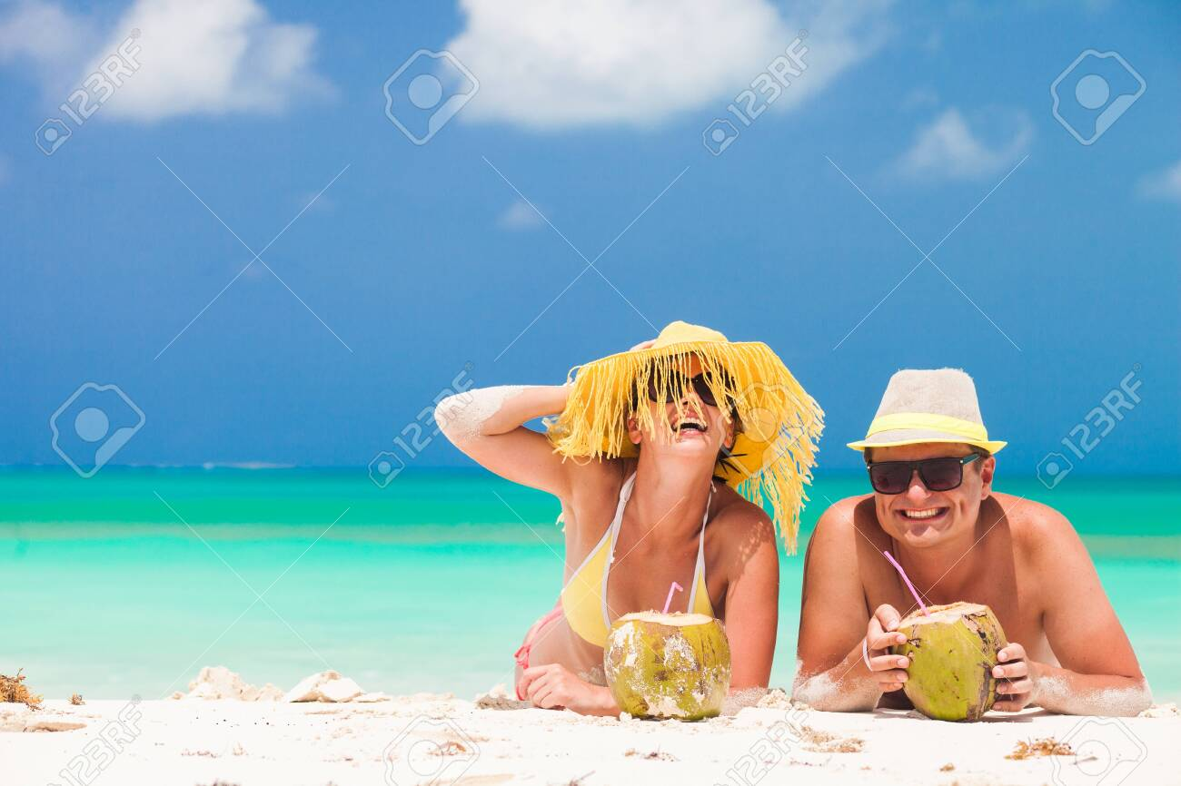 happy young couple lying on a tropical beach in Barbados and drinking a coconut cocktail - 129155175