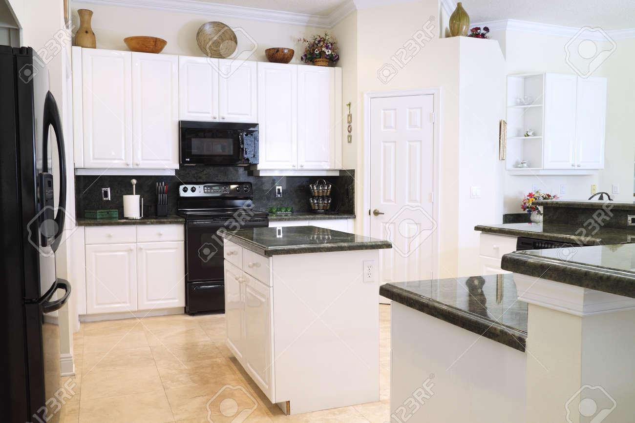Vista de una cocina moderna y hermosa con electrodomésticos de lujo,  muebles blancos, y encimeras de granito verde