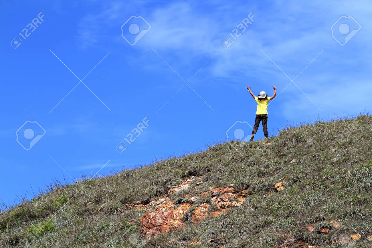 Young woman with black hair is jump on grass in front of blue sky Stock Photo - 14752701