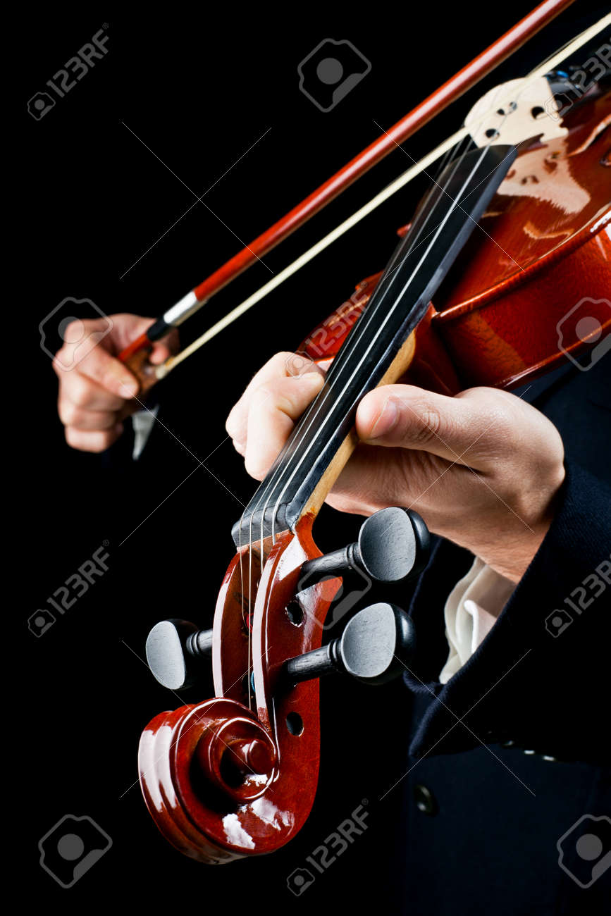 particularly of the hands of the violinist, playing the notes - 12962803