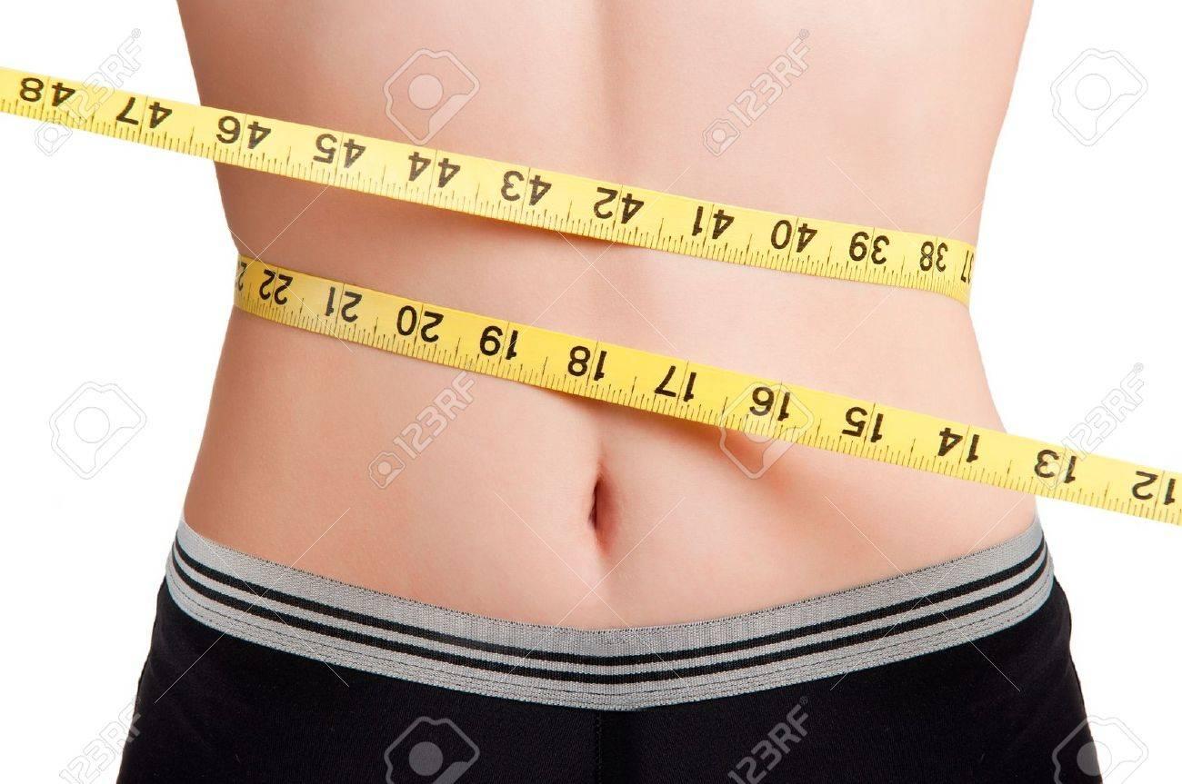 9aede6c13 Foto de archivo - Mujer medir su cintura con una cinta métrica amarilla