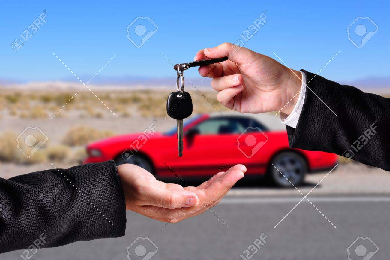 A hand giving a key to another hand. Both persons in suits. Car in the background. Stock Photo - 14723828