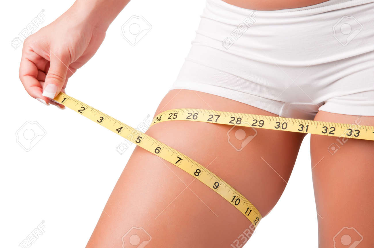 Woman measuring her thigh with a yellow measuring tape Stock Photo - 15232831