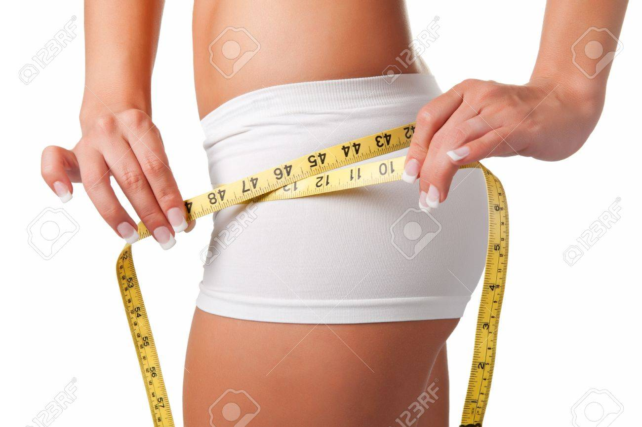 Woman measuring her waist with a yellow measuring tape Stock Photo - 15279018